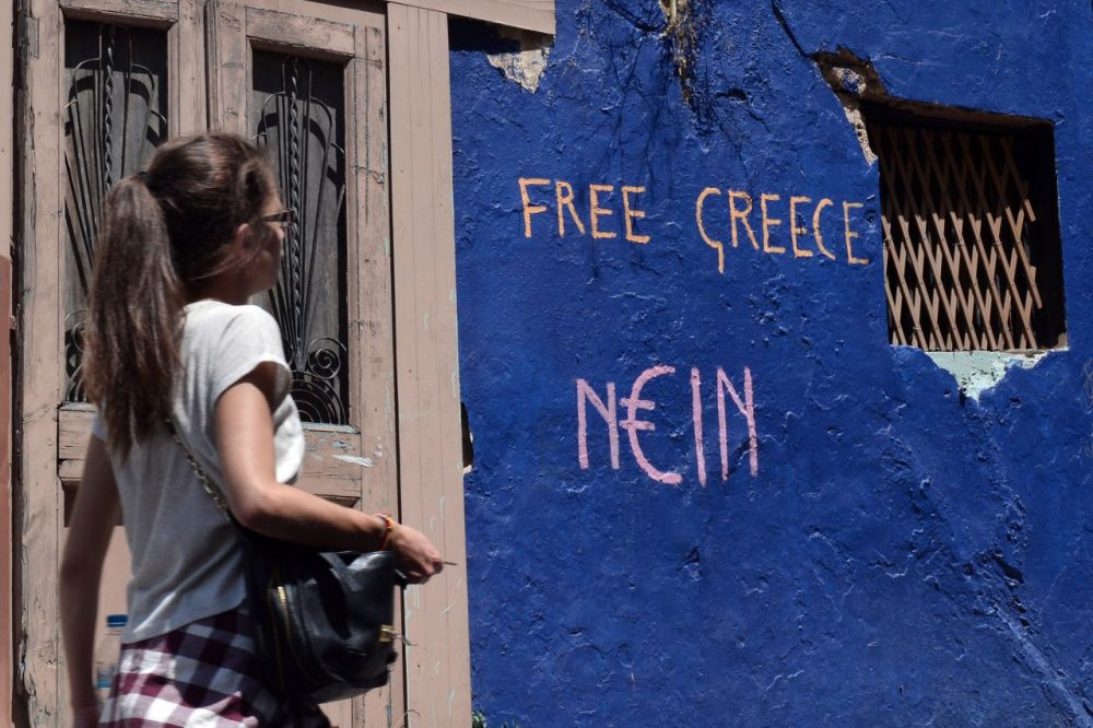 A woman walks past a slogan written on a wall in Athens on July 7, 2015. Eurozone leaders will hold an emergency summit in Brussels on July 7 to discuss the fallout from Greek voters' defiant 'No' to further austerity measures, with the country's Prime Minister Alexis Tsipras set to unveil new proposals for talks. (Louisa Gouliamaki/AFP/Getty Images)