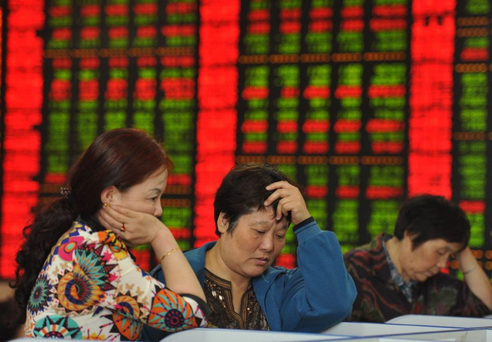 Investors check share prices in a stock firm in Fuyang, east China's Anhui province on June 29, 2015. Chinese shares plunged in morning trading on June 29, extending losses from the past two weeks despite a surprise interest rate cut at the weekend. (STR/AFP/Getty Images)
