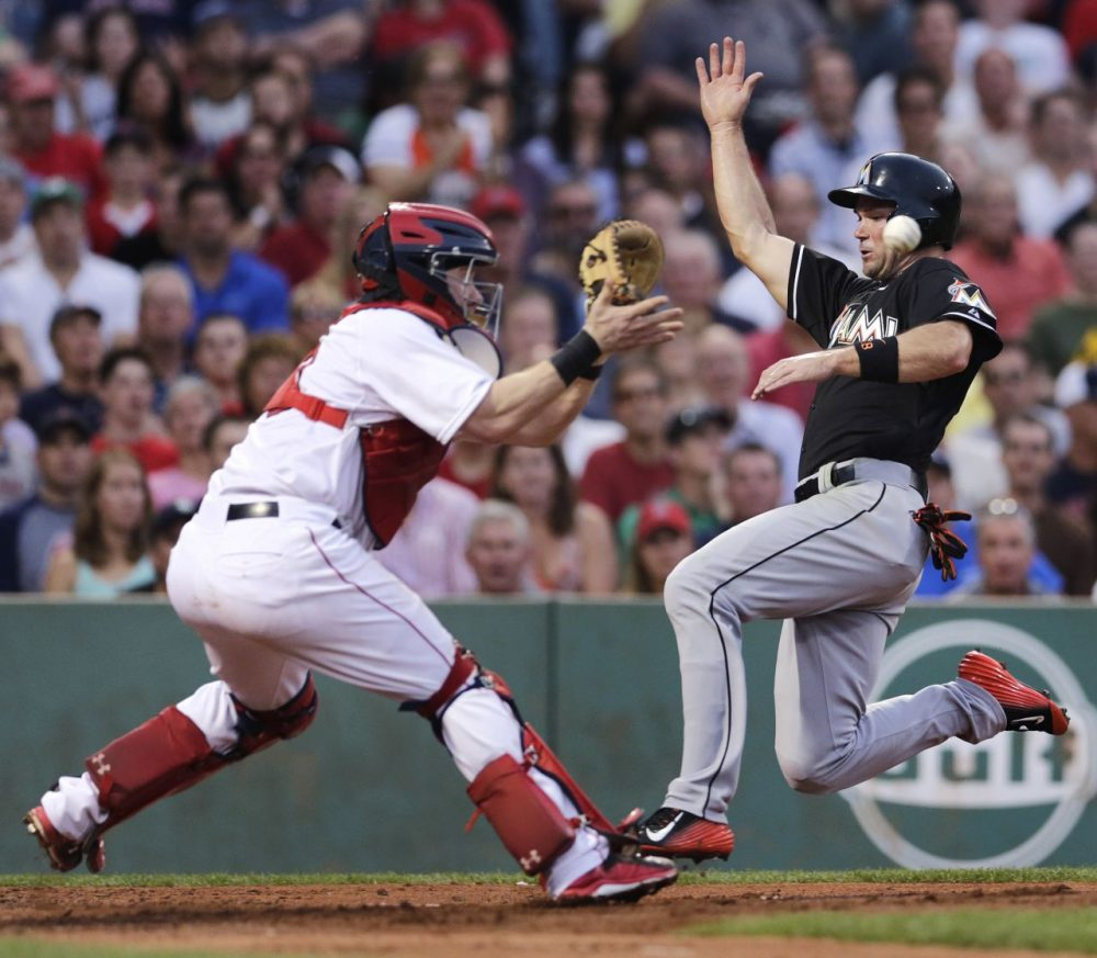 Miami Marlins' Cole Gillespie beats the throw, and tag by Boston Red Sox catcher Ryan Hanigan, to score on a single by Christian Yelich during the third inning of a game in Boston, Tuesday July 7, 2015. (Charles Krupa/AP)