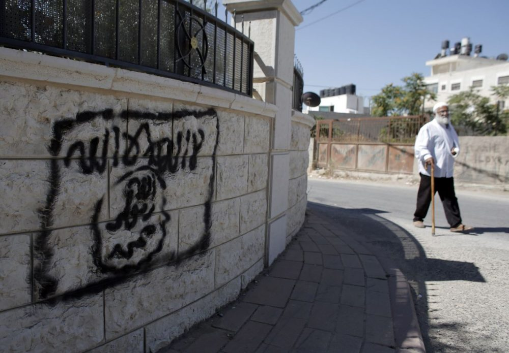 A Palestinian man walks past a graffiti portraying the Islamic State group's flag in the East Jerusalem neighbourhood of Beit Hanina on July 5, 2015. (Ahmad Gharabli/AFP/Getty Images)