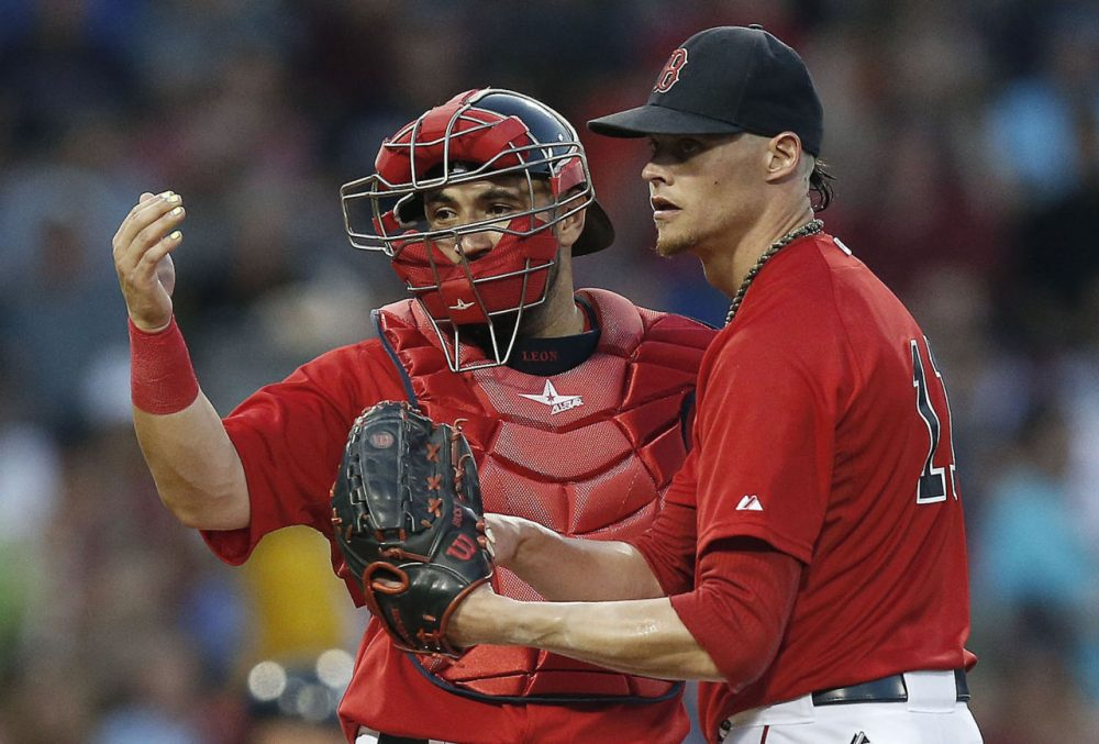Boston Red Sox's Sandy Leon, left, signals to the dugout beside Clay Buchholz during the fourth inning. (AP Photo/Michael Dwyer)