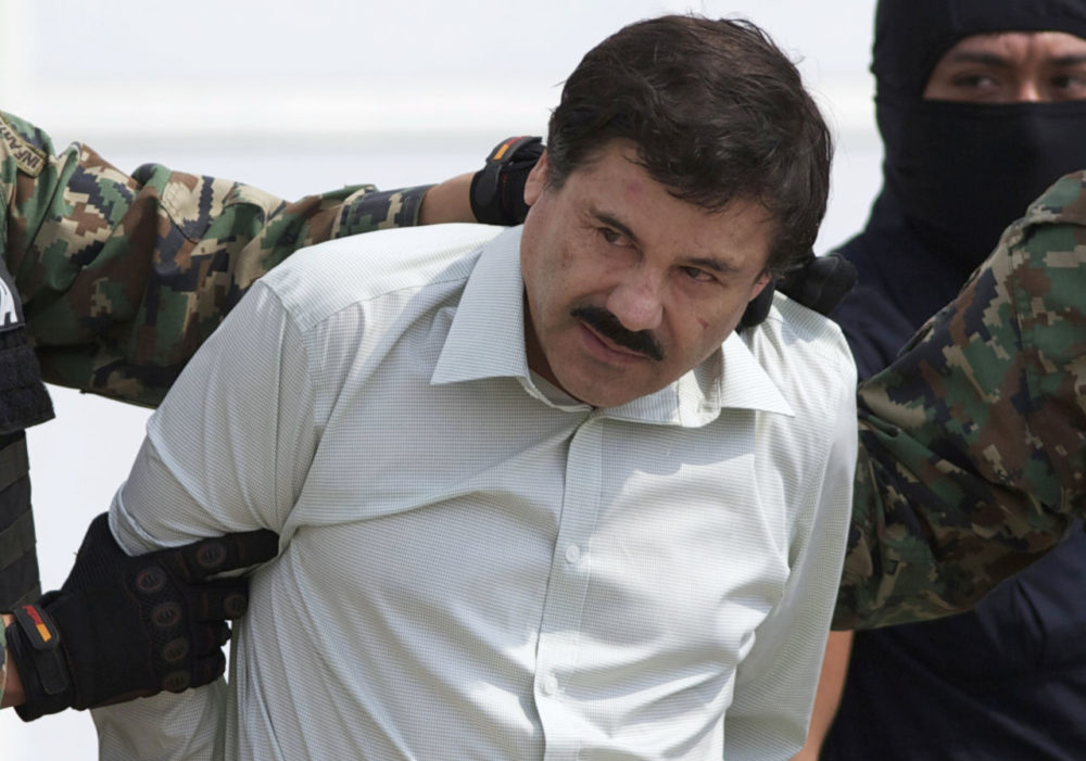 """In this 2014 file photo, Joaquin """"El Chapo"""" Guzman, head of Mexico's Sinaloa Cartel, is escorted to a helicopter in Mexico City, following his capture in the beach resort town of Mazatlan in February that year. (Eduardo Verdugo/AP)"""