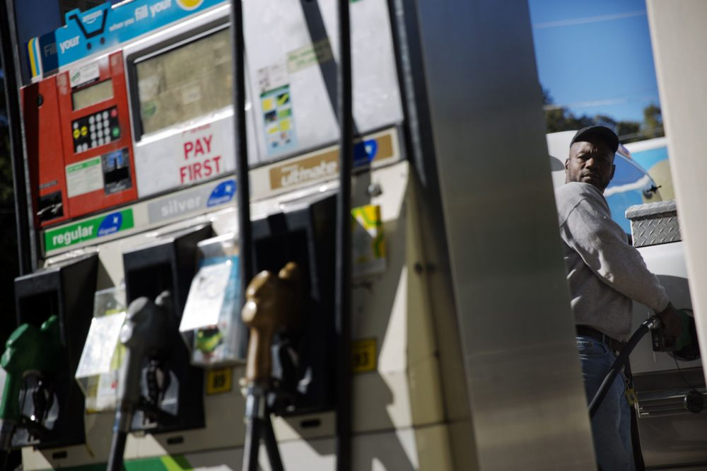 Motorist Jerry Reed watches the pump display while filling up his tank at a gas station, Thursday, Oct. 30, 2014, in Atlanta. (David Goldman/AP)