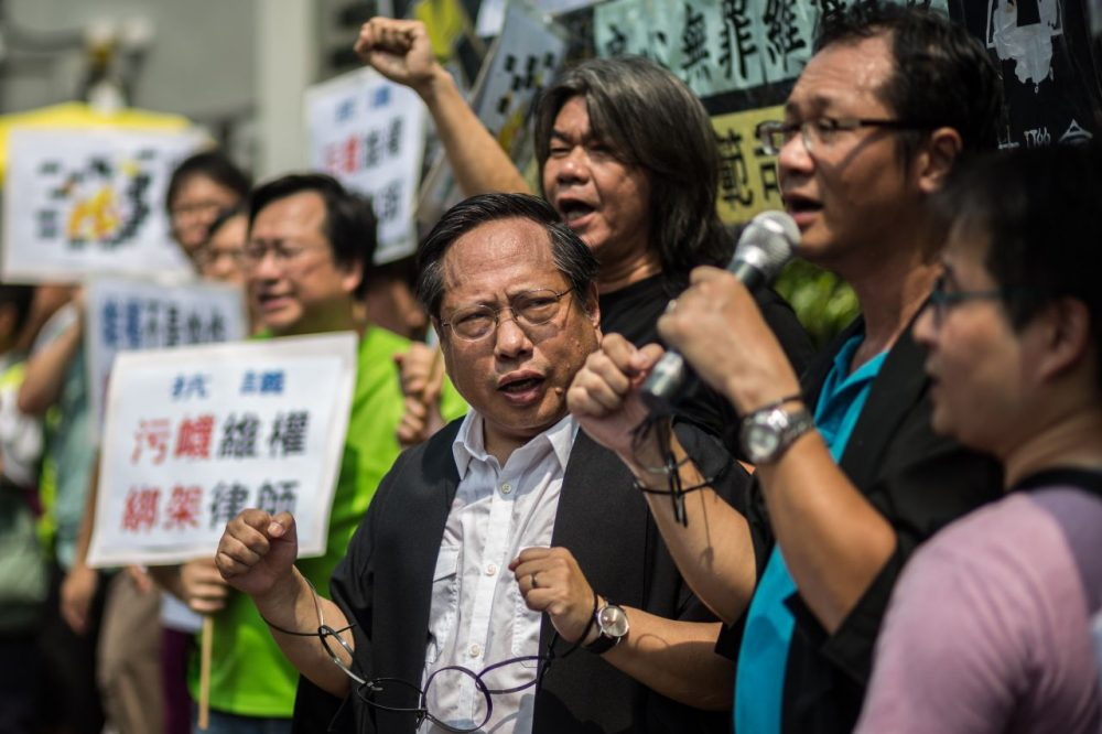 Hong Kong Democratic Party's Albert Ho and legislator Leung Kwok-hung, attend a protest in Hong Kong after at least 50 Chinese human rights lawyers and activists were detained or questioned in recent days. (Anthony Wallace/AFP/Getty Images)