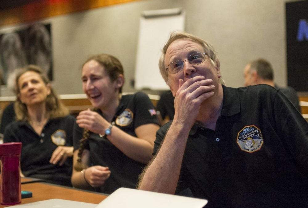 Members of the New Horizons science team, including MIT Professor Richard Binzel, graduate student Alissa Earle (MIT), and Cristina Dalle Ore (SETI Institute), react to seeing the spacecraft's last and sharpest image of Pluto before closest approach later in the day. (Courtesy Bill Ingalls/NASA)