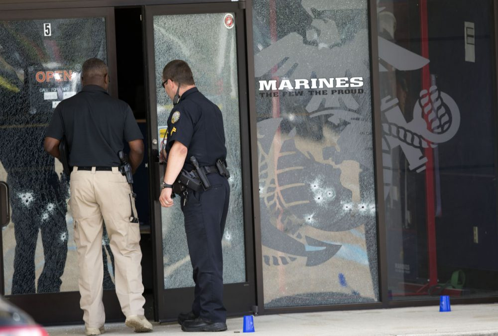 Police officers enter the Armed Forces Career Center through a bullet-riddled door after a gunman opened fire on the building Thursday, July 16, 2015, in Chattanooga, Tennessee. (John Bazemore/AP)