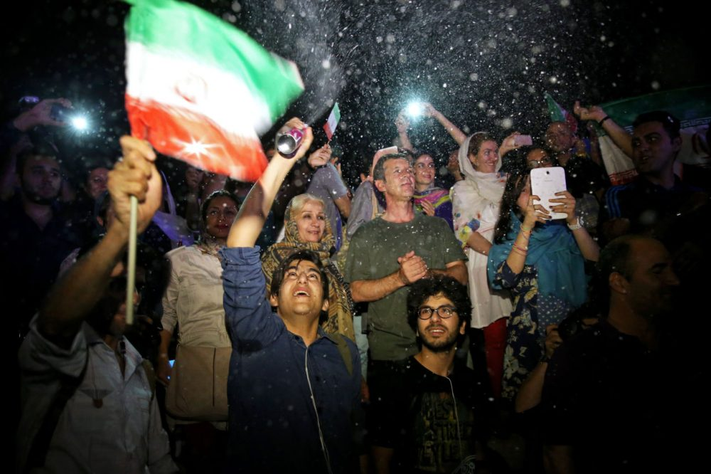 A group of jubilant Iranians cheer and spray artificial snow during street celebrations following a landmark nuclear deal, in Tehran, Iran, Tuesday, July 14, 2015. After long, fractious negotiations, world powers and Iran struck an historic deal Tuesday to curb Iran's nuclear program in exchange for billions of dollars in relief from international sanctions - an agreement aimed at averting the threat of a nuclear-armed Iran and another U.S. military intervention in the Middle East. (Ebrahim Noroozi/AP)