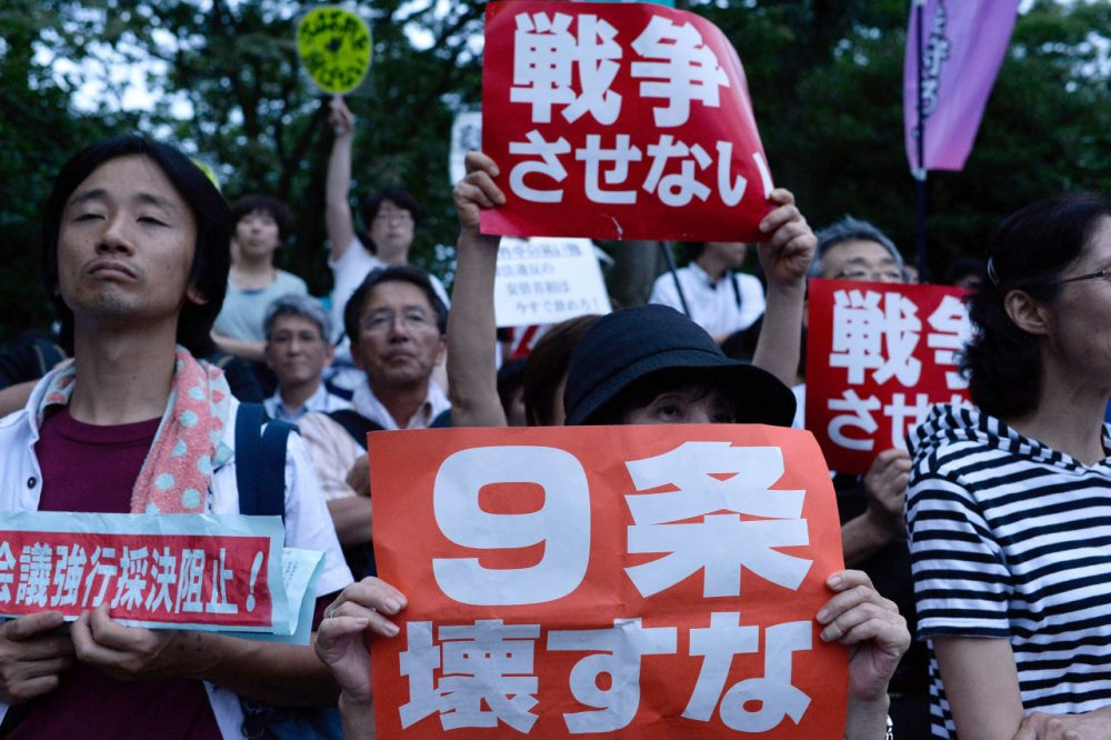 People hold signs during a protest outside the National Diet on July 16, 2015 in Tokyo, Japan. The protest is against the security bill approved by the Lower House on July 16, 2015, that would allow Japan's Self Defense Forces to also defend aggression against its allies - a concept called collective self-defense, pushed by leading Liberal Democratic Party despite the surging opposition by lawmakers and ordinary voters. (Takashi Aoyama/Getty Images)