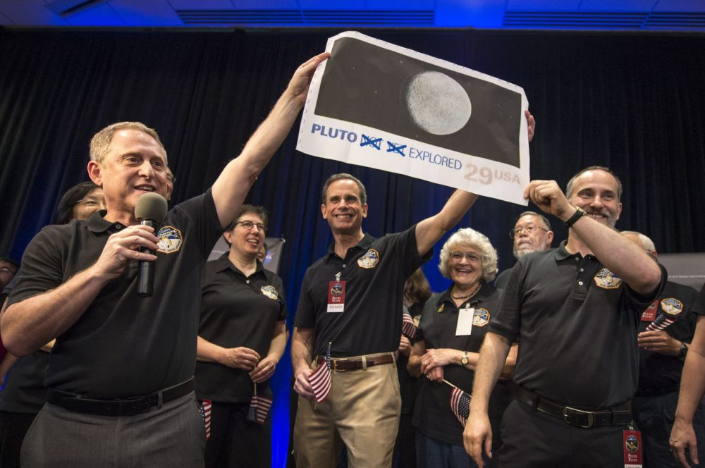In this photo provided by NASA, New Horizons Principal Investigator Alan Stern of Southwest Research Institute (SwRI), Boulder, Colo., left, Johns Hopkins University Applied Physics Laboratory (APL) Director Ralph Semmel, center, and New Horizons Co-Investigator Will Grundy of the Lowell Observatory hold a print of a U.S. stamp with their suggested update since the New Horizons spacecraft made its closest approach to Pluto, at the Johns Hopkins University Applied Physics Laboratory (APL) in Laurel, Maryland. (Bill Ingalls/NASA via AP)