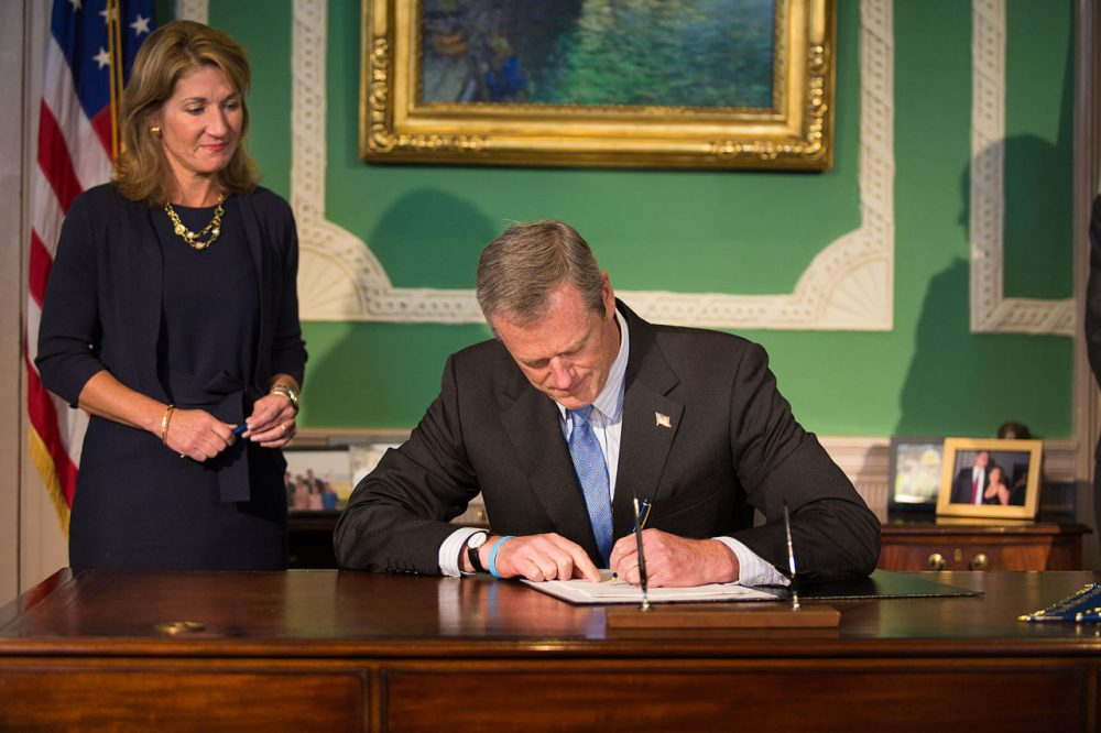 Gov. Charlie Baker signs the Fiscal Year 2016 budget on Friday at the State House, as Lt. Gov. Karyn Polito looks on. (Jesse Costa/WBUR)