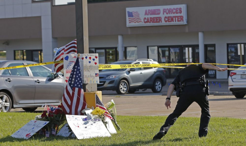 A police officer ducks under tape near a memorial in front of an Armed Forces Career Center on Thursday, July 16, 2015, in Chattanooga, Tenn. (John Bazemore/AP)