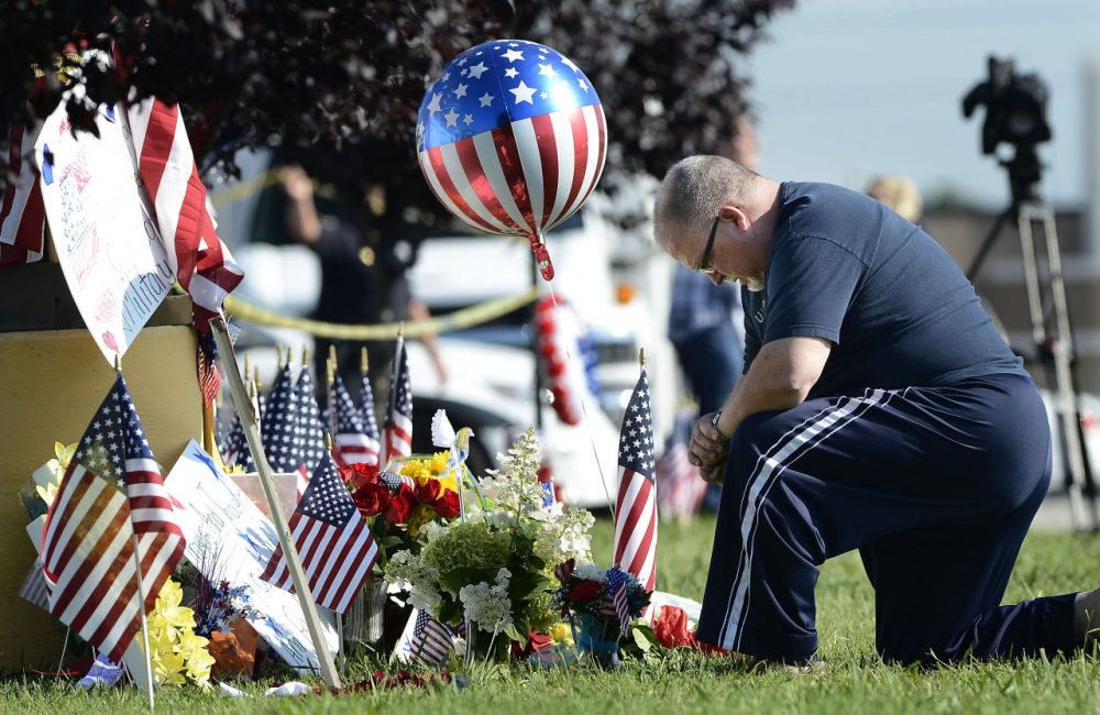 Bill Lettmkuhl kneels by a makeshift memorial in front of near the Armed Forces Career Center on Friday in Chattanooga, Tenn. Muhammad Youssef Abdulazeez, of Hixson, Tenn., attacked two military facilities on Thursday, in a shooting rampage that killed four Marines. (Mark Zaleski/AP)
