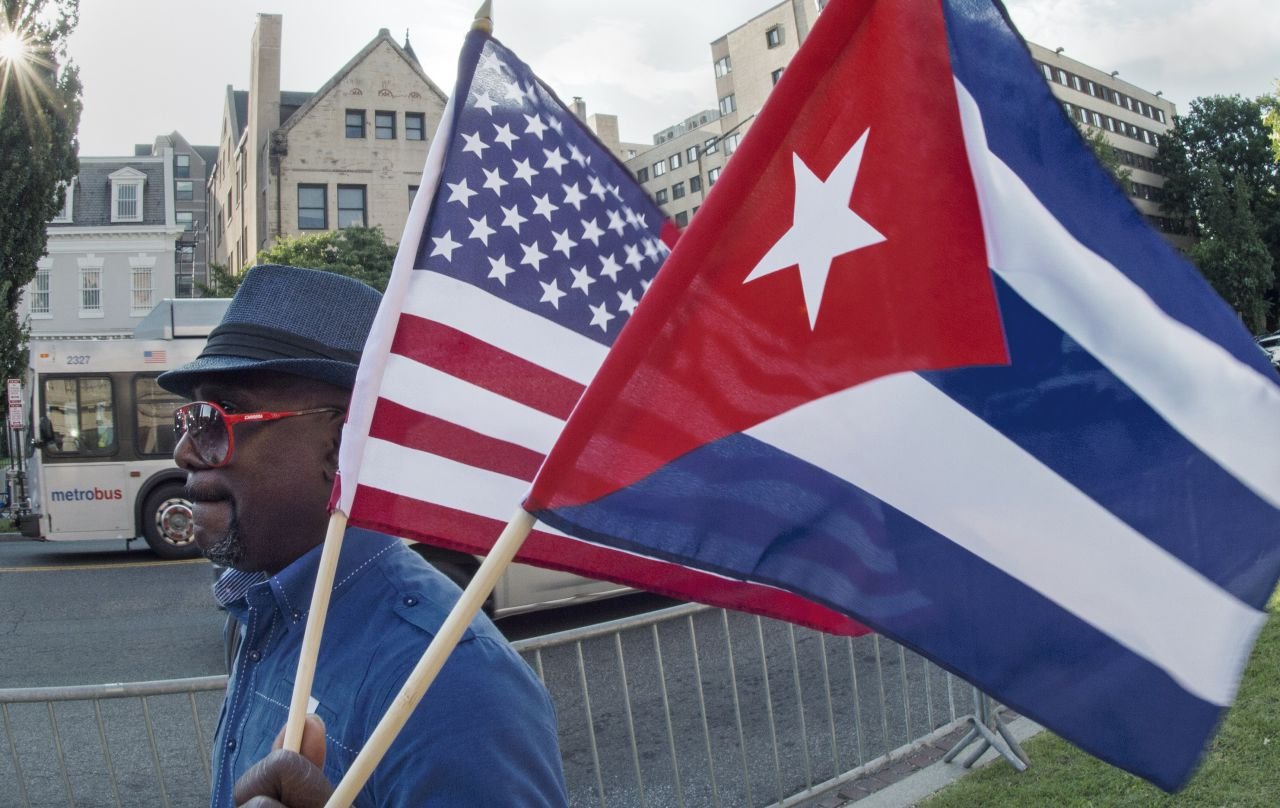 A man waves the U.S. and Cuban flags as he walks in front of the new Cuban Embassy shortly before its official ceremonial opening July 20, 2015, in Washington, D.C. (Paul J. Richards/AFP/Getty Images)