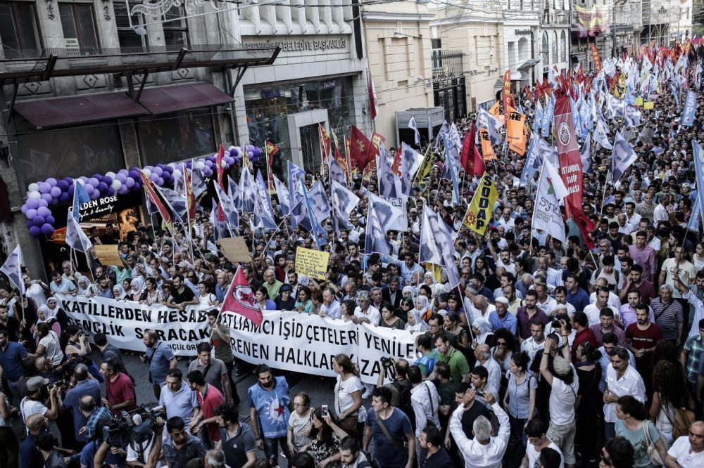 Protesters hold flags and a banner reading 'Islamic state gangs will lose, our resisting people will win' during a demonstration on July 20, 2015 in Istiklal avenue in Istanbul, after a suicide bombing in the Turkish town of Suruc near the border with Syria killed 32 people. (Yasin Akgul/AFP/Getty Images)