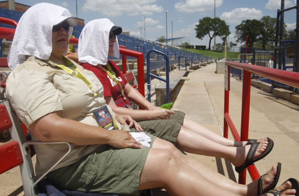 Liz Moody, left, and Stephanie Russell, right, both of Forest Grove, Oregon, cover their heads with towls to keep cool as they watch the Japan-Canada World Cup of Softball game in Oklahoma City, Thursday, July 21, 2011. (Sue Ogrocki/AP)