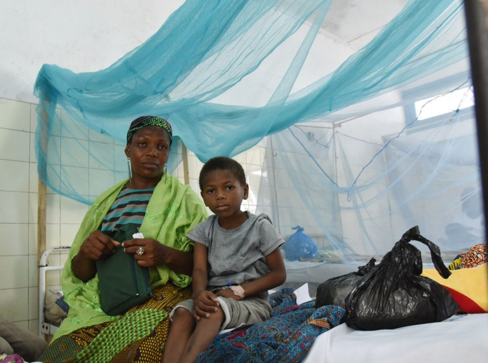 A mother sits with her sick child in a bed with mosquito net in a hospital on April 24, 2015 in the popular suburb of Port-Bouet in Abidjan, on the eve of the World Malaria Day on April 25, 2015. (Sia Kambou/AFP/Getty Images)