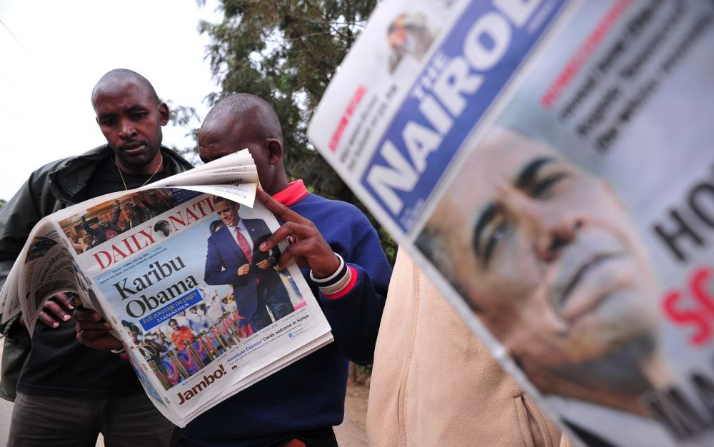 """People read local newspapers with pictures of US President Barack Obama and with headlines """"Welcome Obama"""" on July 24, 2015 in Nairobi.  (SIMON MAINA/AFP/Getty Images)"""