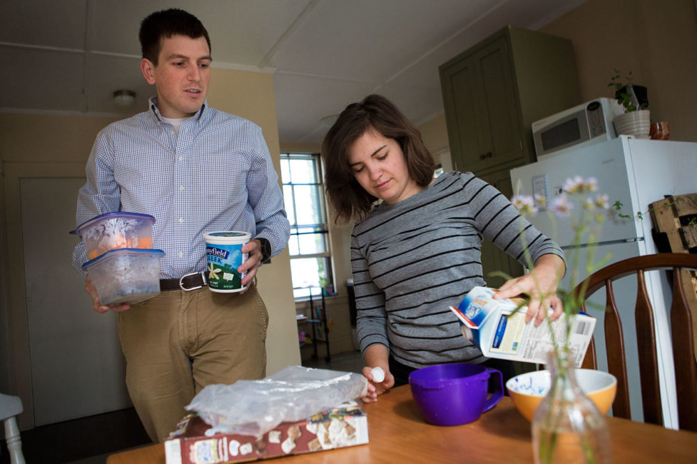 Dan Tothill, 26, and Megan Brabec, 24, prepare homemade lunches for the workday. Both are struggling with high student debt burdens and underemployment. (Jesse Costa/WBUR)