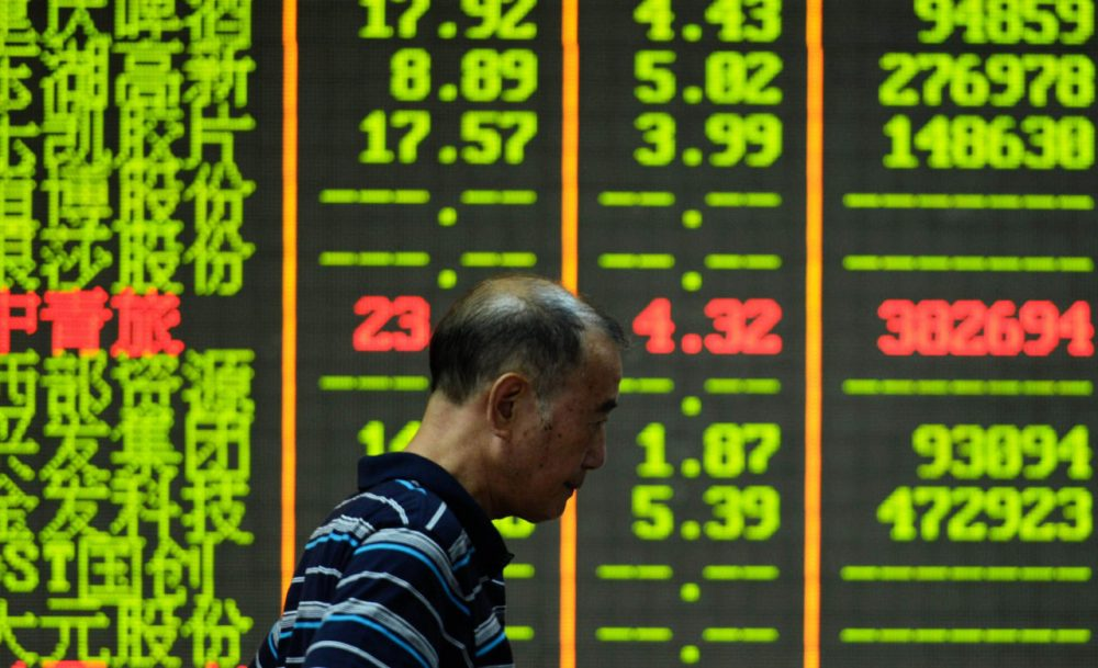 An investor walks past a screen that shows share prices in a security firm in Hangzhou, east China's Zhejiang province on July 27, 2015.  China's benchmark Shanghai stock index slumped 5.22 percent in afternoon trade on July 27, dragged lower by worries over the economy.    AFP PHOTO    CHINA OUT        (STR/AFP/Getty Images)