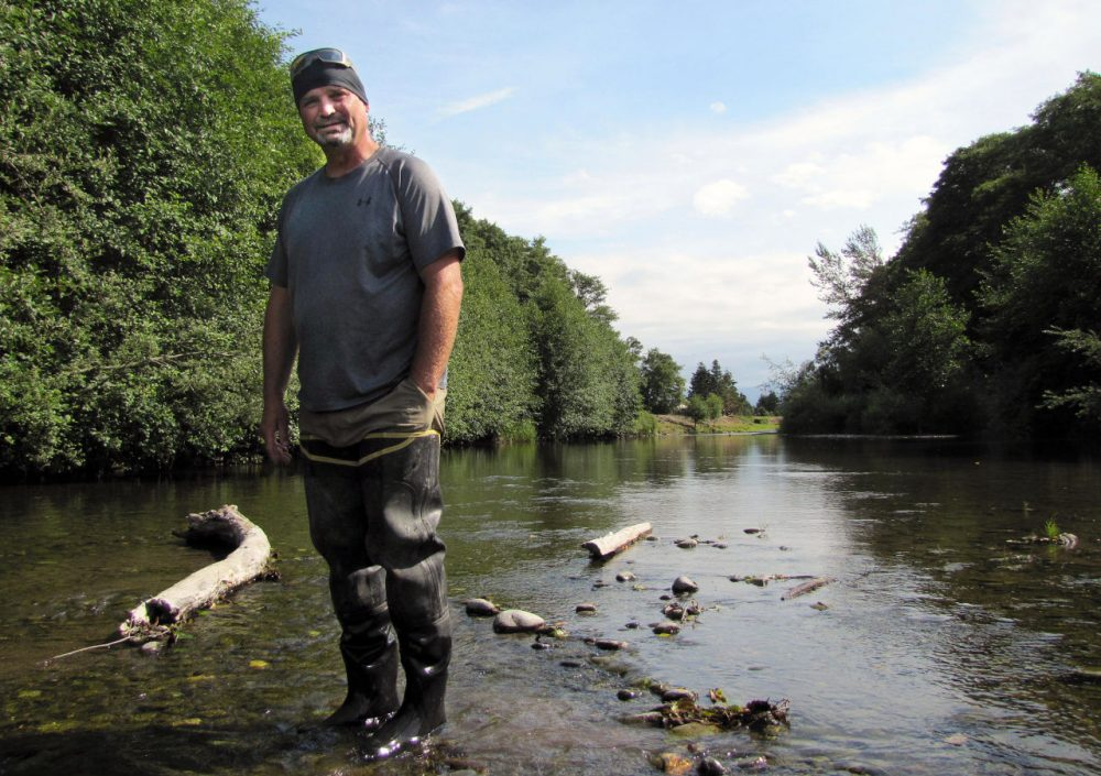 Chris Burns, natural resources technician with Washington's Jamestown S'Klallam Tribe, stands in the Dungeness River. Flows are roughly one-third of normal, prompting fears that salmon won't be able to make it upstream to spawn. (Ashley Ahearn/EarthFix-KUOW)