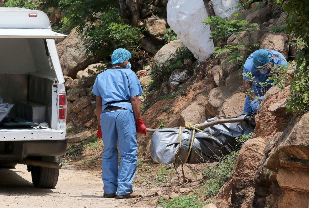 Forensic personnel load onto a van the body of one of the 10 bodies found in clandestine graves in the tourist city of Acapulco, Guerrero State on June 22, 2015. Guerrero is one of Mexico's poorest and most violent states, where a lucrative drug trade has flourished. (STR/AFP/Getty Images)