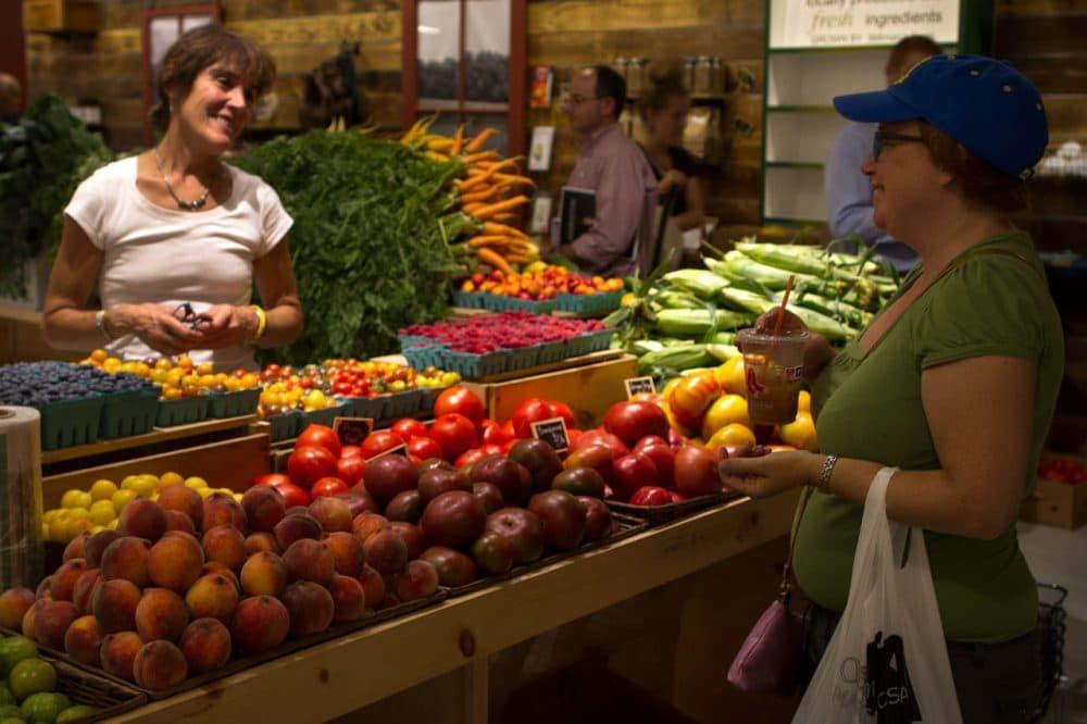 A vendor at the Stillman's Farm stand talks with a customer at the Boston Public Market. (Hadley Green for WBUR)