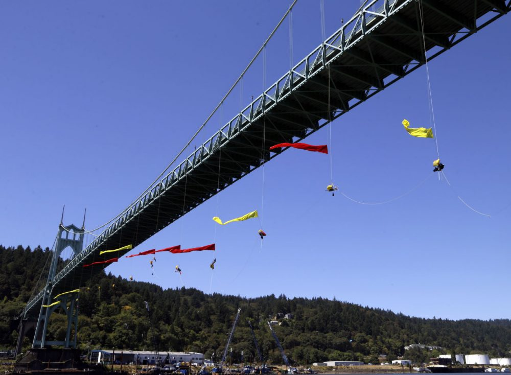 Activists unfurl colored banners while hanging from the St. Johns bridge in Portland, Ore. on Wednesday to protest the departure of Royal Dutch Shell PLC icebreaker Fennica, which is in Portland for repairs. (Don Ryan/AP)