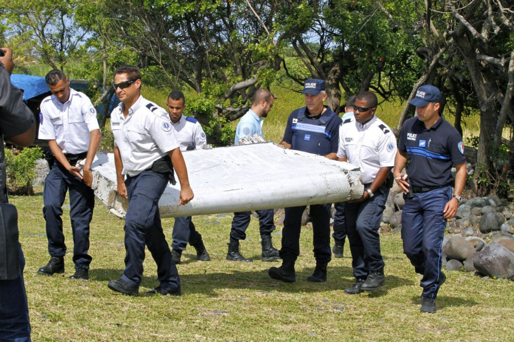 """French police officers carry a piece of debris from a plane in Saint-Andre, Reunion Island on Wednesday, July 29, 2015. Air safety investigators, one of them a Boeing investigator, have identified the component as a """"flaperon"""" from the trailing edge of a Boeing 777 wing, a U.S. official said. Flight 370, which disappeared March 8, 2014, with 239 people on board, is the only 777 known to be missing. (Lucas Marie/AP)"""