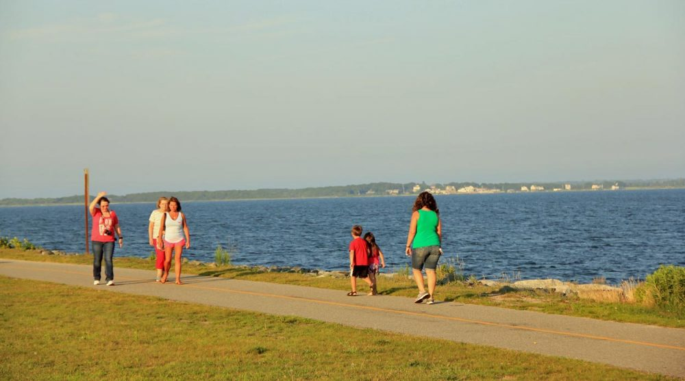 People walk along Fort Taber Park in New Bedford. The city was the proposed site to host Olympic sailing, had Boston won its bid to host the 2024 Games. (Simon Rios/WBUR)