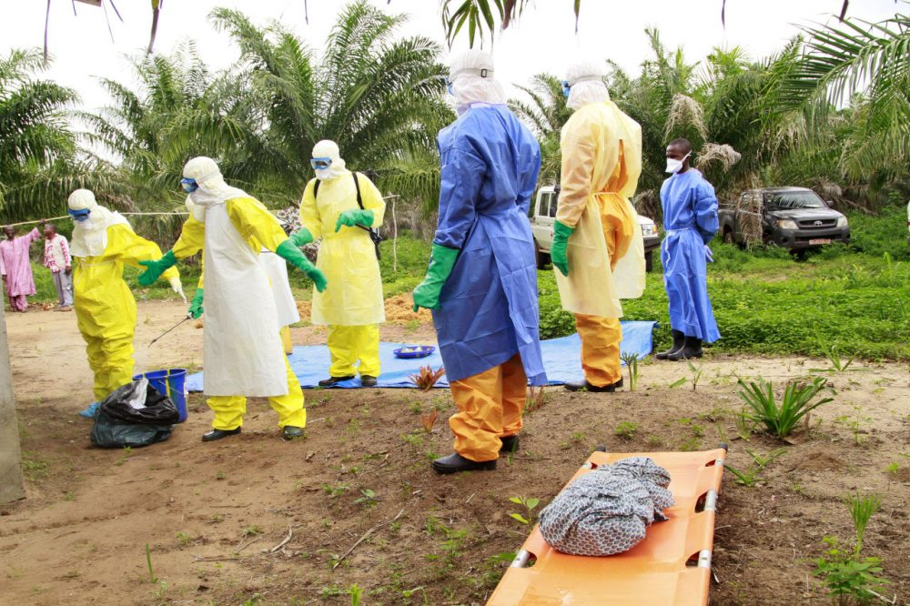 The wrapped remains of a new born child suspected of contracting the Ebola virus, lays on a stretcher as health workers, dressed in Ebola protective gear, move the body for burial in Dubreka, Guinea on June 19. (Youssouf Bah/AP)