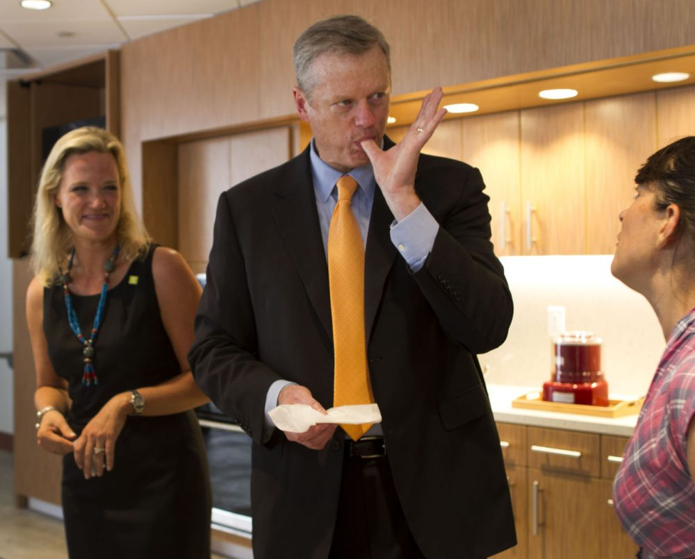 Gov. Charlie Baker enjoys a donut from Union Square Donuts at the opening of the Boston Public Market opening this week. (Hadley Green/WBUR)