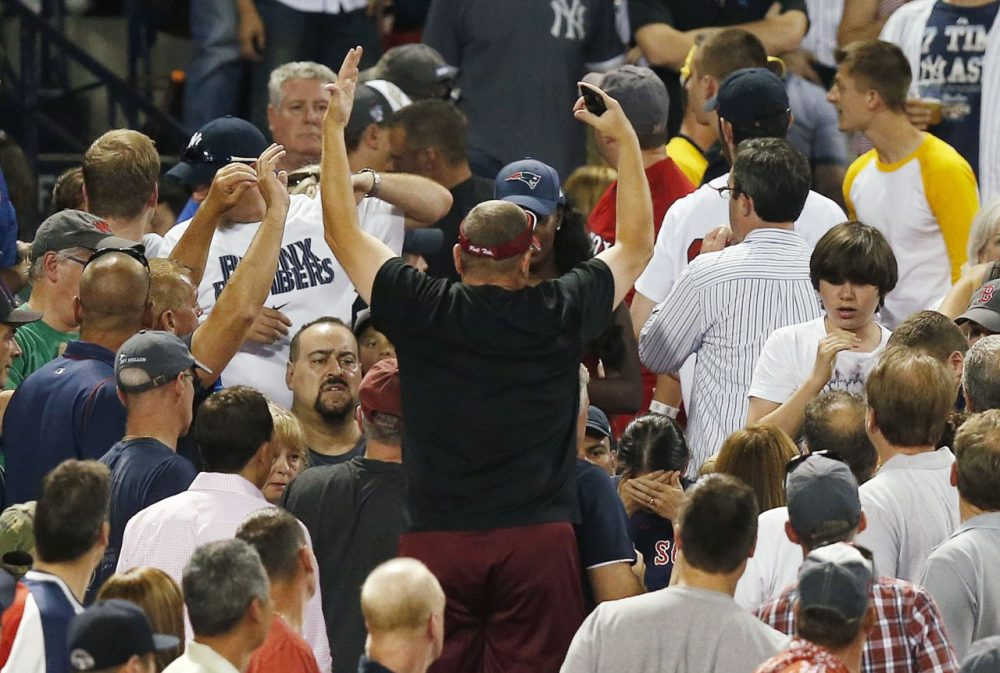 A woman, lower right, holds her head after being hit by a foul ball during the fifth inning of Friday night's Red Sox-Yankees game at Fenway Park. (Michael Dwyer/AP)