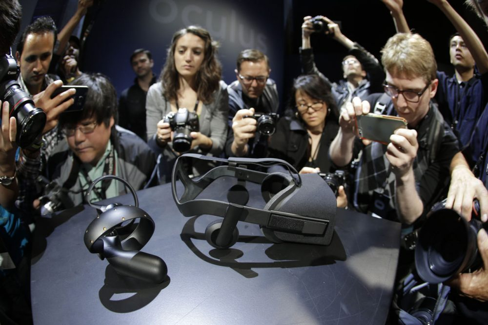 Photographers take pictures of the new Oculus Rift virtual reality headset and touch input device following a news conference Thursday, June 11, 2015, in San Francisco. (AP Photo/Eric Risberg)