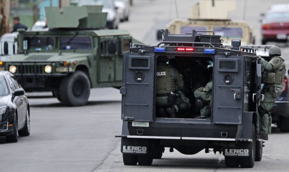 A SWAT team drives through a Watertown neighborhood in April 2013 while searching for a suspect in the Boston Marathon bombings. (Charles Krupa/AP)