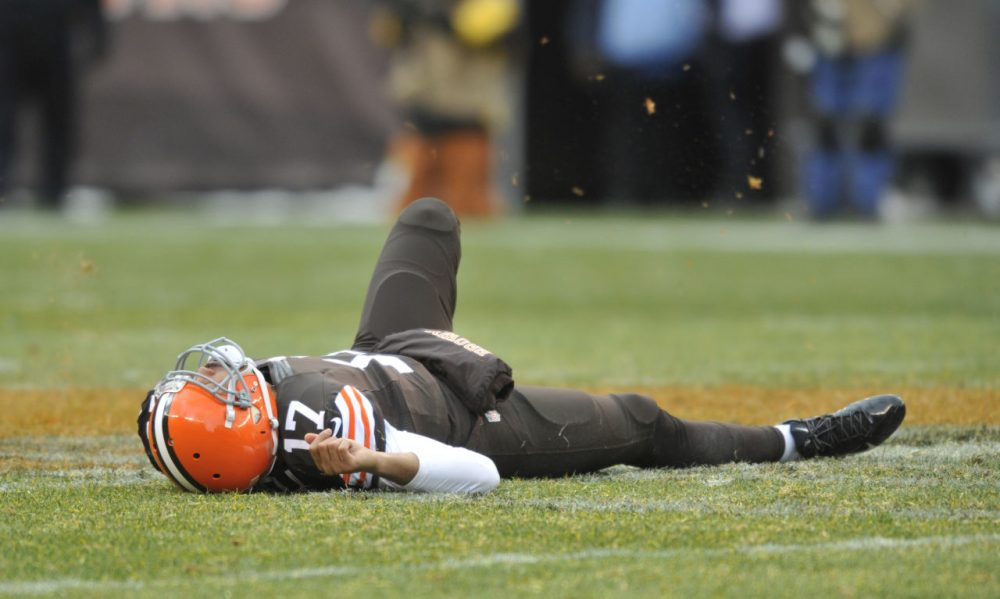 Cleveland Browns QB Jason Campbell lies near midfield after suffering a concussion in a game on Nov. 24, 2013. Traumatic brain injuries, whether they occur on a sports field or in a war zone, are on the rise. (David Richard/AP)