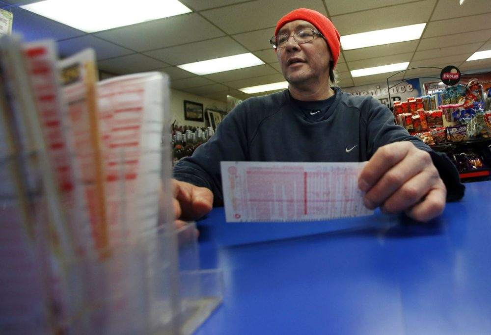 Robert Allen buys a Powerball ticket at a North Andover convenience store on Feb. 19, 2014. (Elise Amendola/AP)