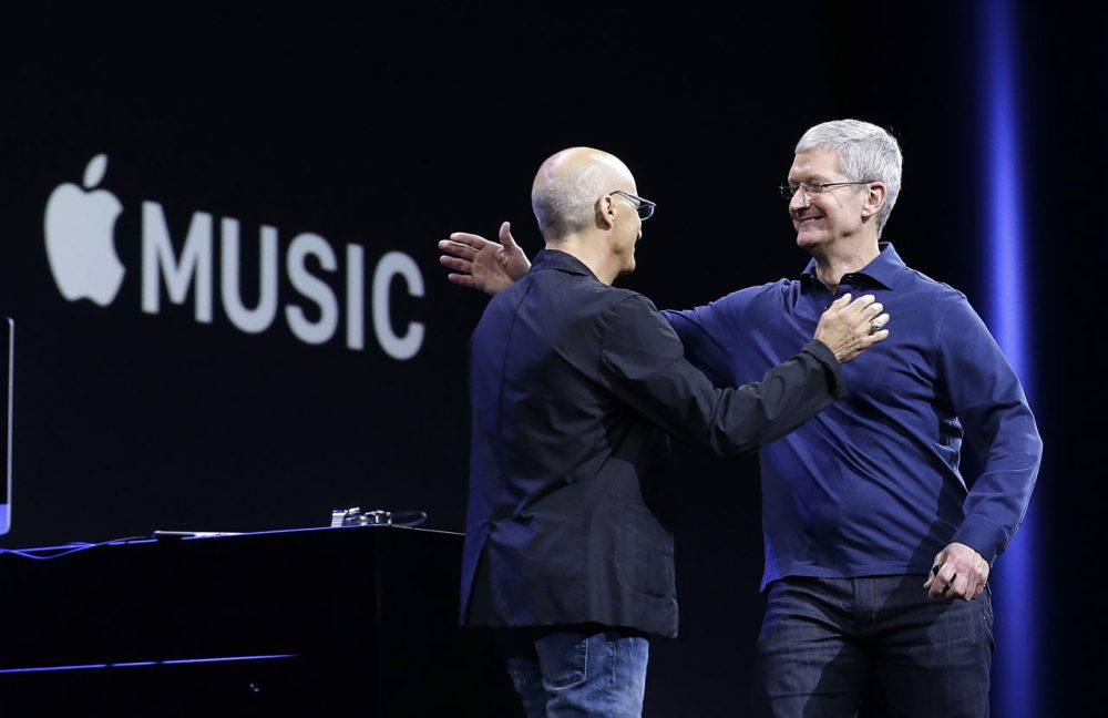 Apple CEO Tim Cook, right, hugs Jimmy Iovine at the announcement of Apple Music in June.  (Jeff Chiu/AP)