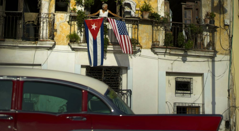 "Judy Bolton-Fasman: ""My mother wants the doors to open to the Cuba she once knew, not the country she sees as grotesquely frozen in time."" In this picture, Javier Yanez looks out from his balcony, where he hung American and Cuban national flags to celebrate the restored full diplomatic relations between Cuba and the United States, in Old Havana, Monday, July 20, 2015, the day the U.S. restored diplomatic relations with the island nation. (Ramon Espinosa/AP)"