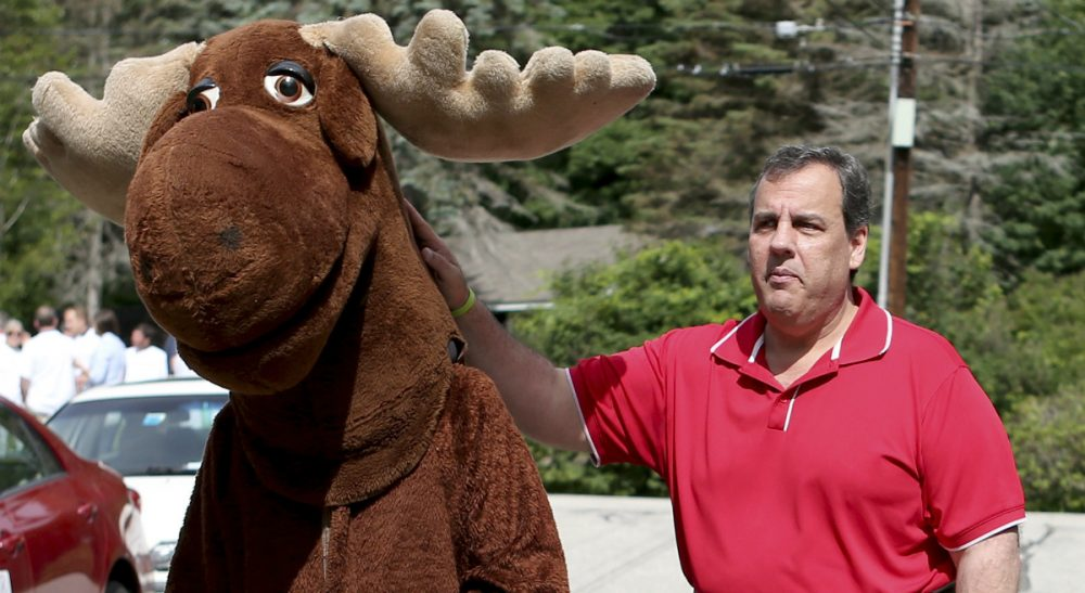 """Rich Barlow: """"How might an issues-oriented Republican make sense of such a sprawling field?""""  Pictured: Republican presidential candidate, New Jersey Gov. Chris Christie, consoles a man dressed in a moose costume on a warm summer day after having his photo taken with him and before the start of the Fourth of July parade, Saturday, July 4, 2015, in Wolfeboro, N.H. (Mary Schwalm/AP)"""