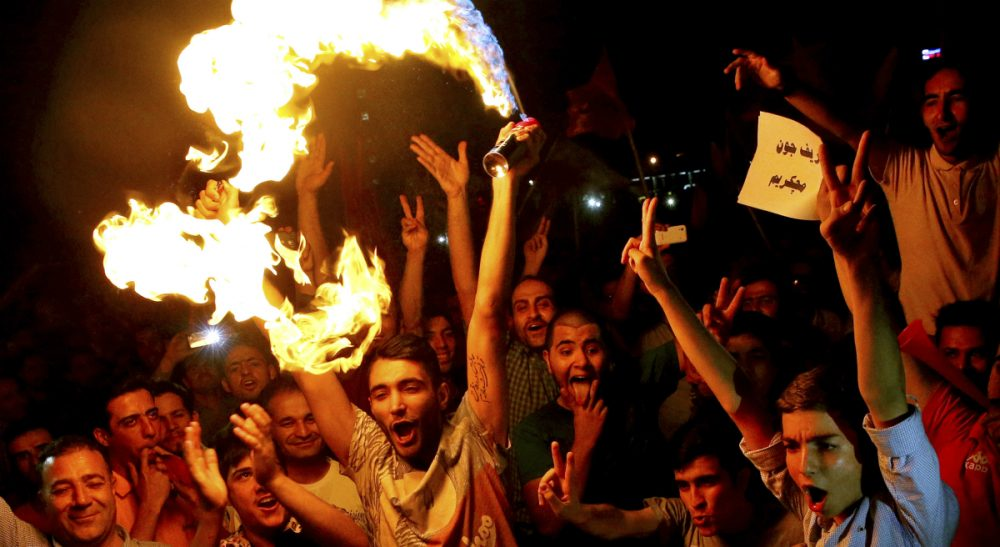 Iranians celebrate following a landmark nuclear deal in Tehran, Iran, Tuesday, July 14, 2015. After long, fractious negotiations, world powers and Iran struck an historic deal Tuesday to curb Iran's nuclear program in exchange for billions of dollars in relief from international sanctions, an agreement aimed at averting the threat of a nuclear-armed Iran and another U.S. military intervention in the Middle East. (Ebrahim Noroozi/AP)