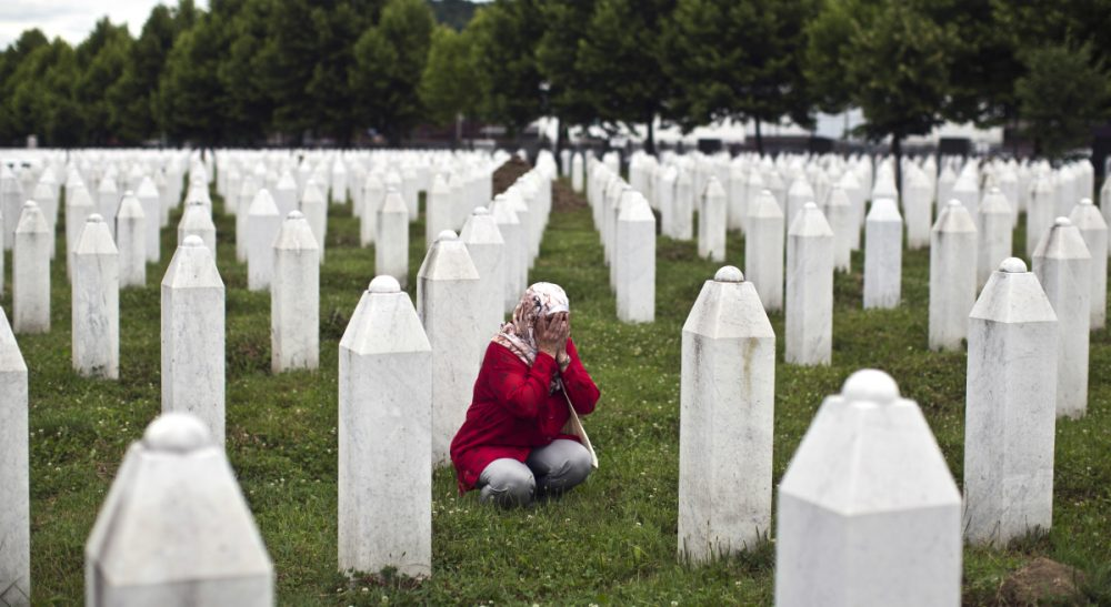 A woman prays next to a grave of her relative at the Potocari memorial complex, in Potocari, close to Srebrenica, 150 kilometers northeast of Sarajevo, Thursday, July 9, 2015. The 20th anniversary of the Srebrenica massacre, the worst crime in Europe after the Nazi era, will be marked on Saturday, July 11, 2015. (Marko Drobnjakovic/AP)