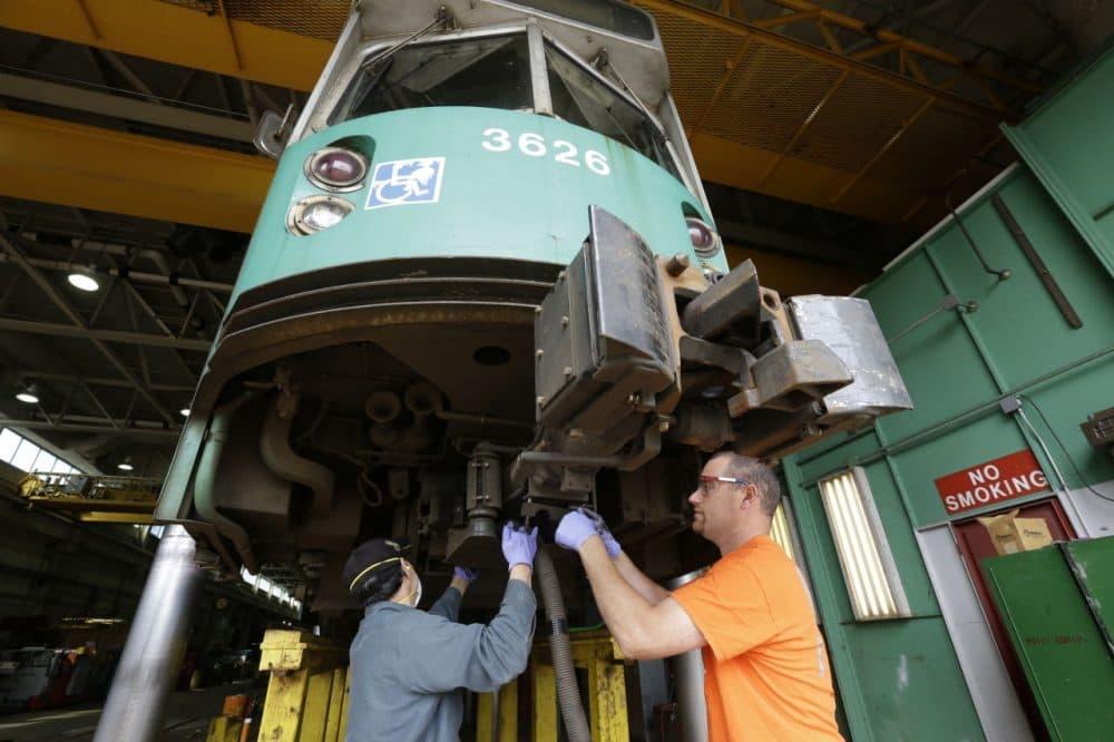 Light rail repairer Rob Cunningham, of Belchertown, Mass., right, works on the coupling of a railcar at the Massachusetts Bay Transportation Authority's Riverside maintenance facility in Newton, Mass. (Steven Senne/AP)