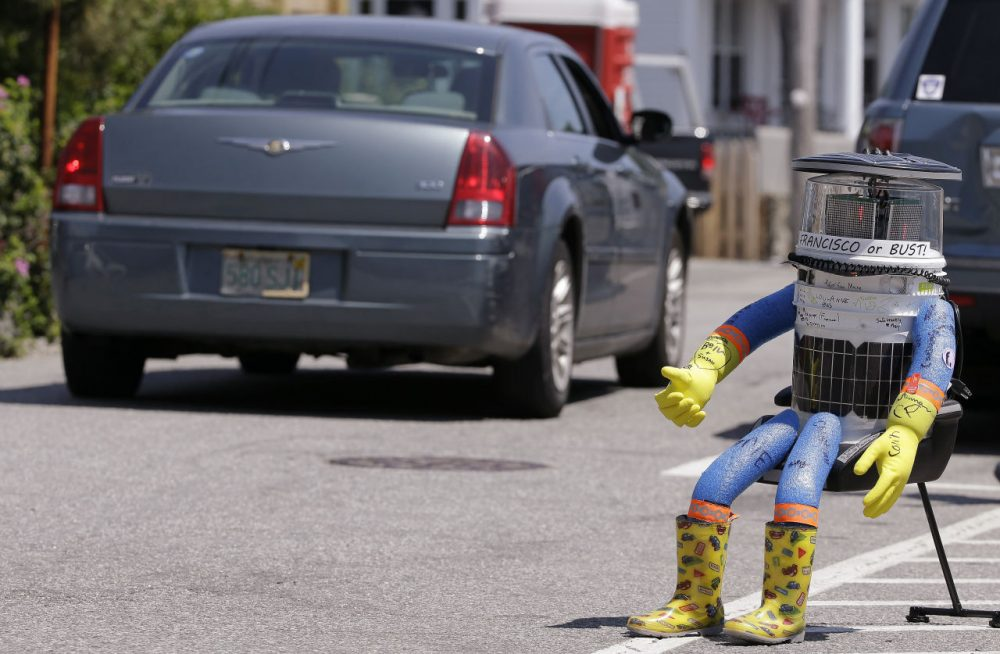 "HitchBOT started in Marblehead, Massachusetts, on July 17 with its thumb raised skyward, a grin on its digital face and tape wrapped around its head that read ""San Francisco or bust."" (Stephan Savoia/AP)"