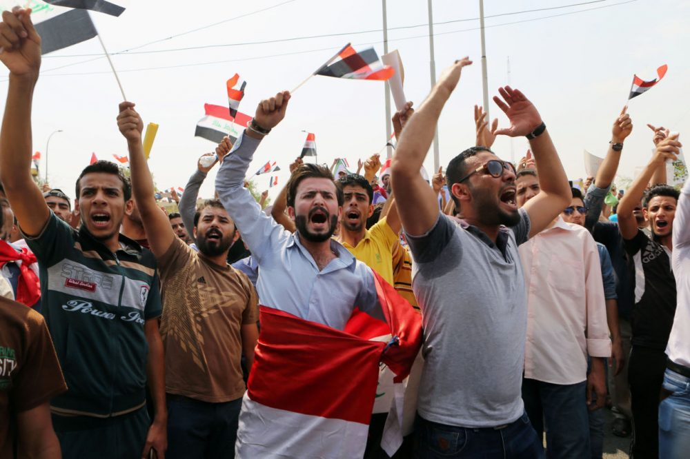 Protesters chant anti-government slogans as they wave national flags during a protest against corruption and the lack of government services and power outages in front of the provincial council building in Basra, 340 miles (550 kilometers) southeast of Baghdad, Iraq, Saturday, Aug. 1, 2015. (Nabil al-Jurani/AP Photo)