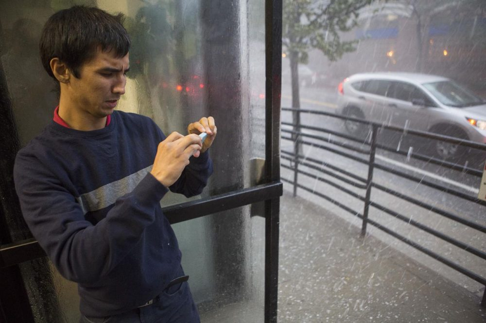 A man takes a photo of the hail falling outside on St. Paul Street in Boston Tuesday. (Jesse Costa/WBUR)
