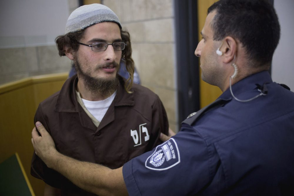 Meir Ettinger appears in court in Nazareth Illit, Israel, on Tuesday, Aug. 4, 2015. Israel said Tuesday it was interrogating  Ettinger, the suspected head of a Jewish extremist group, in the first arrest of an Israeli suspect following last week's arson attack in the West Bank that killed a Palestinian toddler and wounded his brother and parents. (Ariel Schalit/AP)