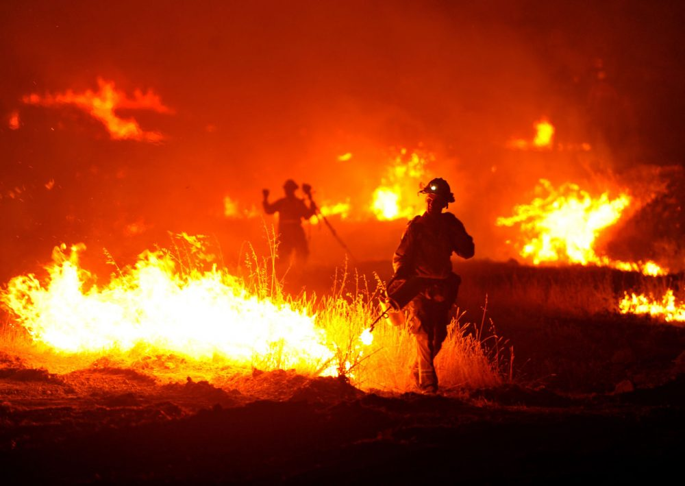 A firefighter lights a backfire as the Rocky Fire burns near Clearlake, Calif., on Monday, Aug. 3, 2015. The fire has charred more than 60,000 acres and destroyed at least 24 residences. (Josh Edelson/AP)