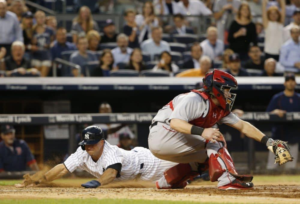 Yankees' Brett Gardner, left, slides in behind Red Sox catcher Ryan Hanigan on Alex Rodriguez's third-inning RBI-double at Yankee Stadium, Thursday, Aug. 6, 2015. (Kathy Willens/AP)