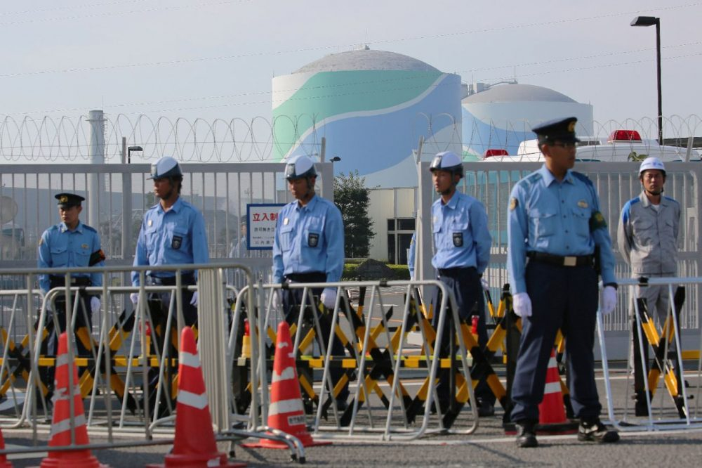 Police officers and security personnel stand in front of the gate of the Kyushu Electric Power Sendai nuclear power plant as anti-nuclear protesters rally against the restarting of the nuclear reactor in Satsumasendai, Kagoshima prefecture, on Japan's southern island of Kyushu yesterday.  Japan restarted a mothballed nuclear reactor for the first time in two years since the Fukushima meltdown. (Jiji Press/Getty Images)