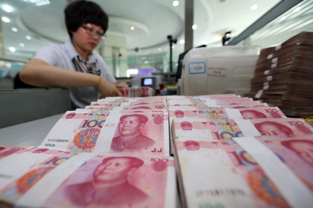 A teller counts yuan banknotes in a bank in Lianyungang, east China's Jiangsu province on August 11, 2015. China's central bank on August 11 devalued its yuan currency by nearly two percent against the US dollar, as authorities seek to push market reforms and bolster the world's second-largest economy. (STR/Getty Images)